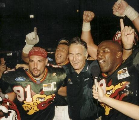 "Naposki (left) played for four years in NFL Europe with the Barcelona Dragons under coach Jack Bicknell (center), who called him ""everything you wanted in a teammate and a player.''"